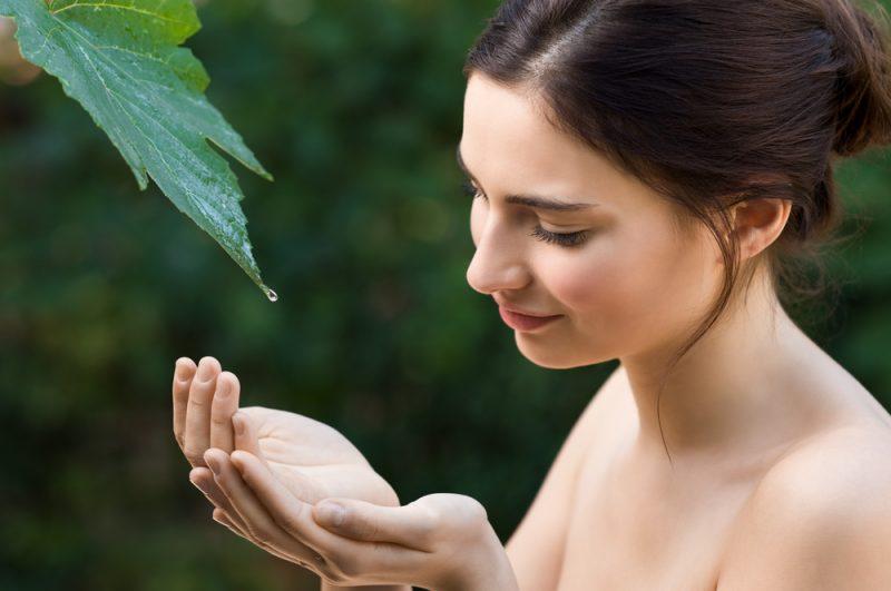 Den härliga unga kvinnan tar en droppe av klart vatten från ett blad i naturen