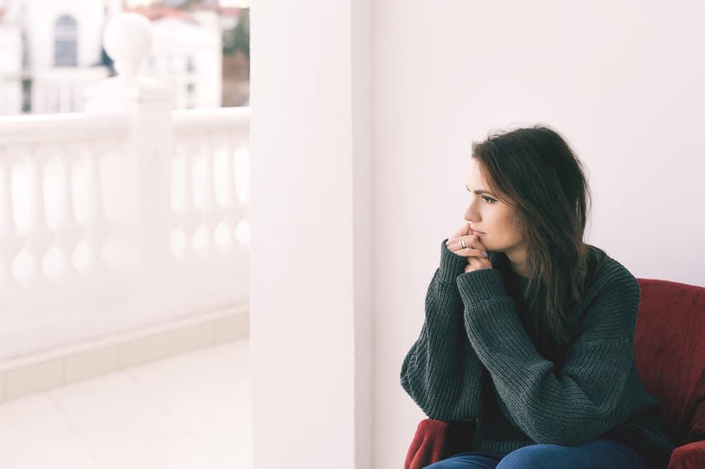 Den härliga kvinnan i grå tröja sitter på en stol på balkongen