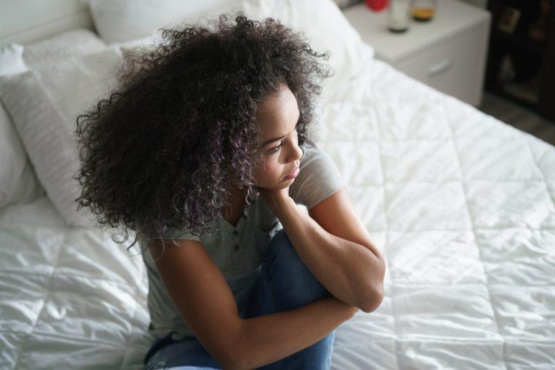 Deprimerad spansktalande flicka hemma och tittade bort med sorgligt uttryck