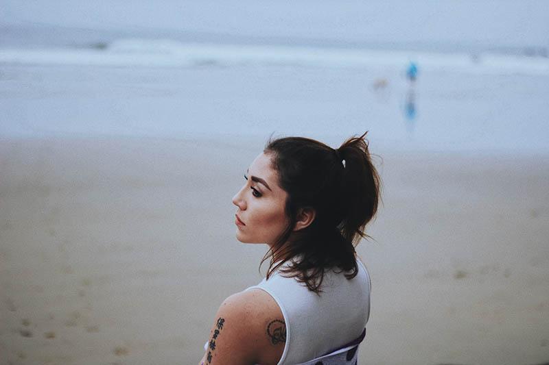 kvinna som står ensam på stranden