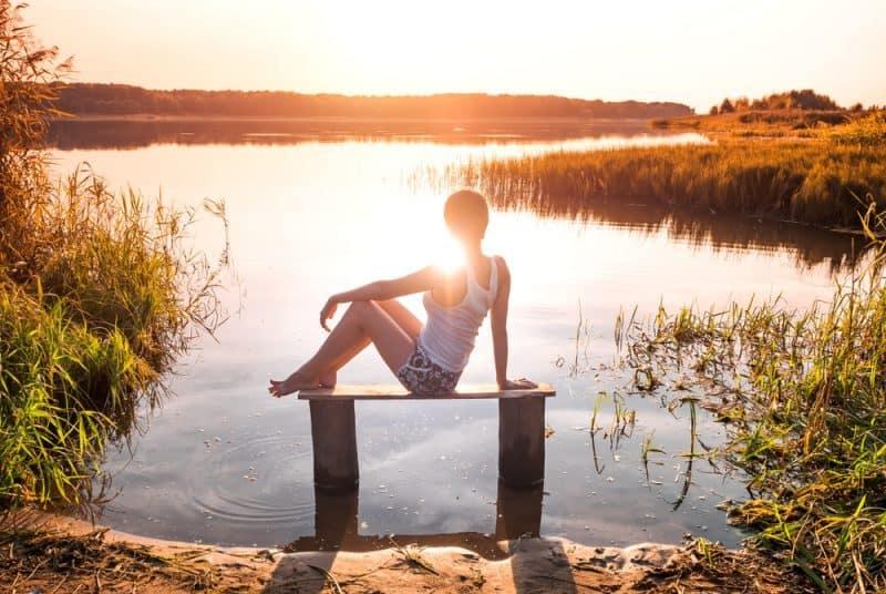 Eftertänksam flicka sitter på en bänk vid floden och njuter av en härlig solnedgång