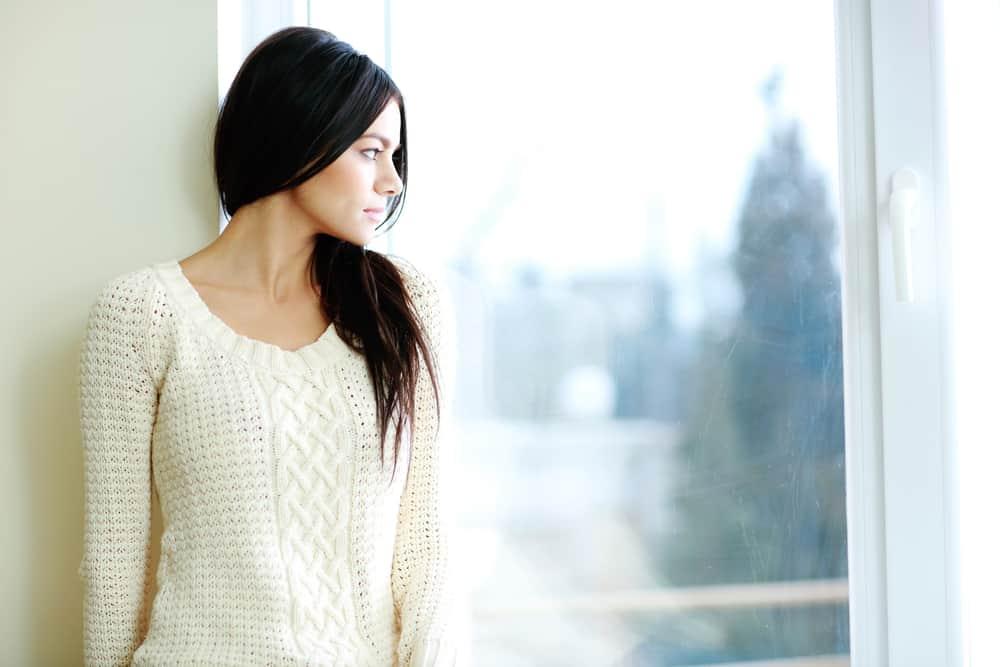 Stående av en ung härlig kvinna som ser fönstret