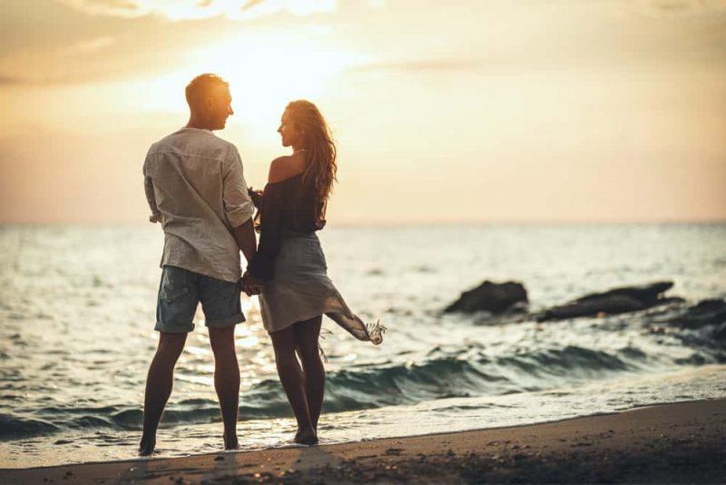 Ett älskande par har kul och kramar på den tomma sandstranden vid solnedgången