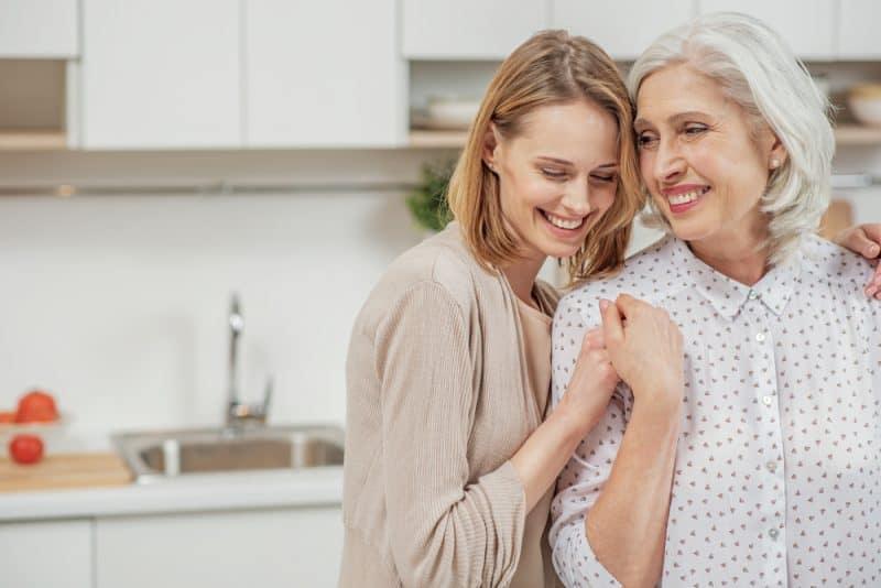 Gullig ung dotter som omfamnar hennes moder med förälskelse