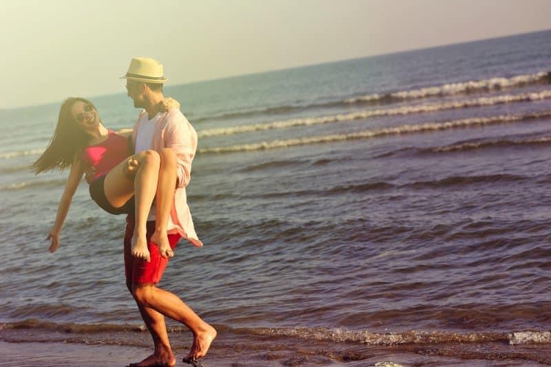 Härligt ungt par som är förälskat som tycker om och har gyckel på stranden