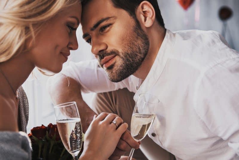 Härligt ungt par som dricker champagne och ler