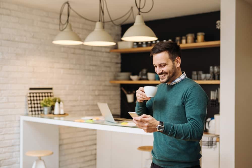 Hållande telefon och kaffe för stilig man