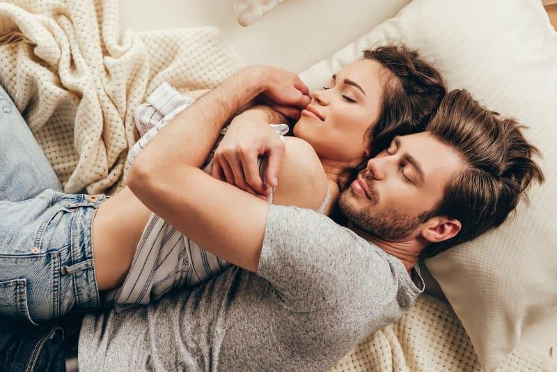 man och kvinna kramar i sängen