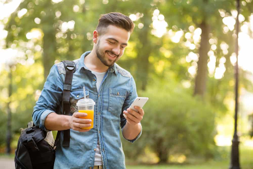 Korthårig man som ser mobiltelefonen