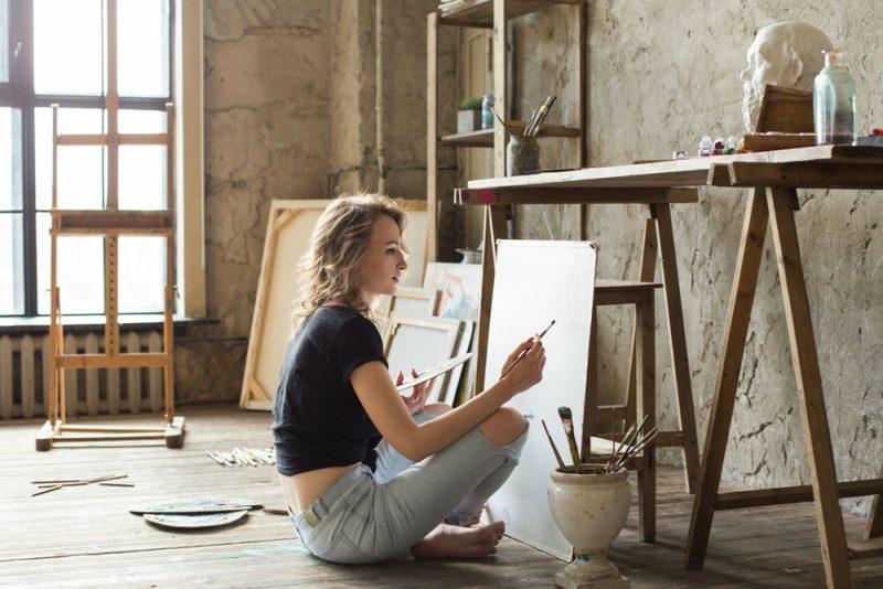 Kvinnamålaresammanträde på golvet framför kanfas och teckning