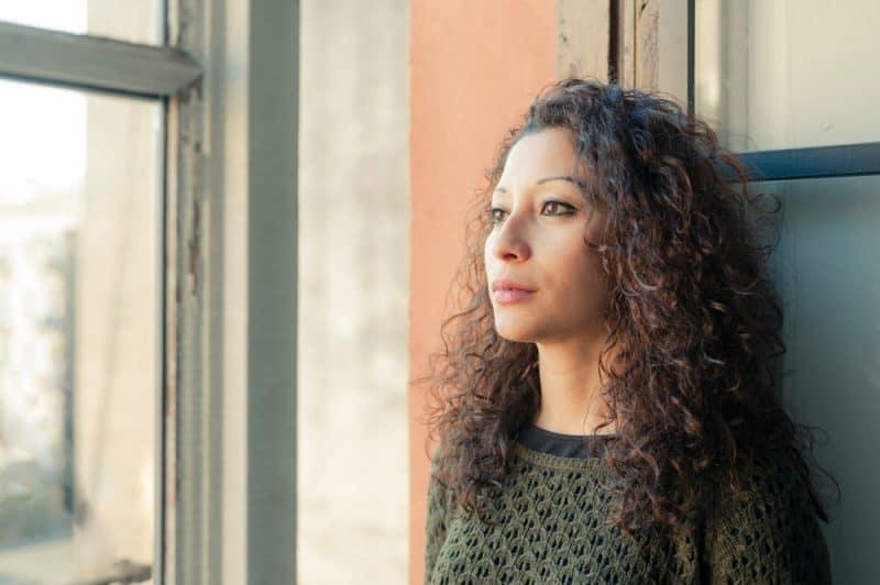 Latinsk kvinna som håller ögonen på genom hennes hemfönster