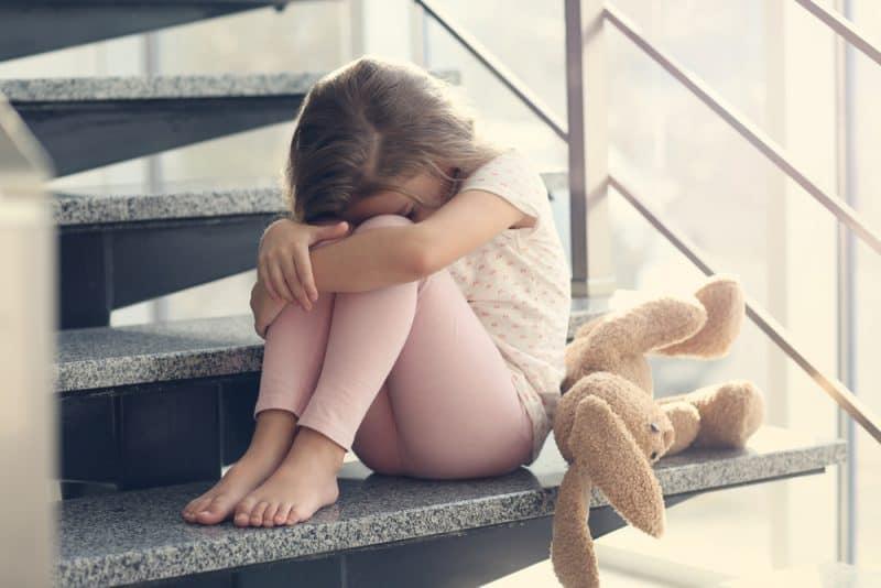Ledsen flickasammanträde på trappan