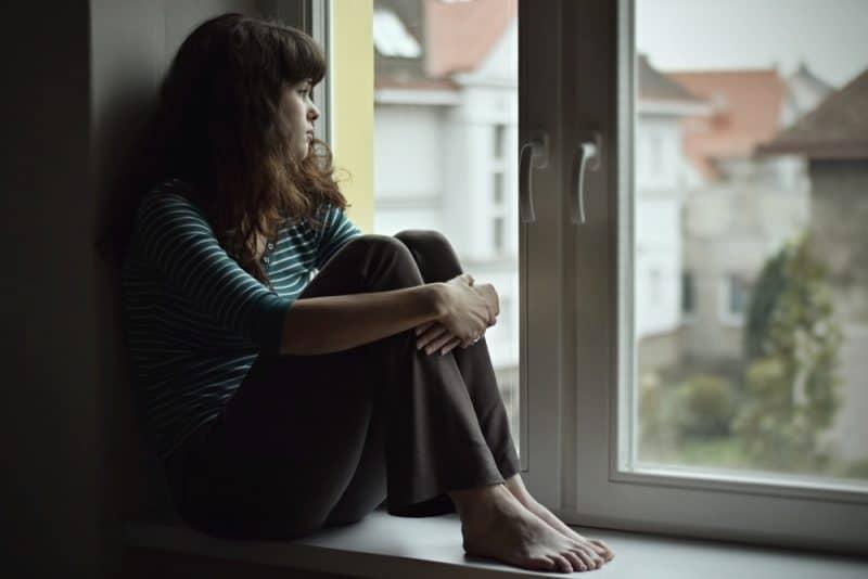 Ledset sammanträde för ung kvinna på fönstret