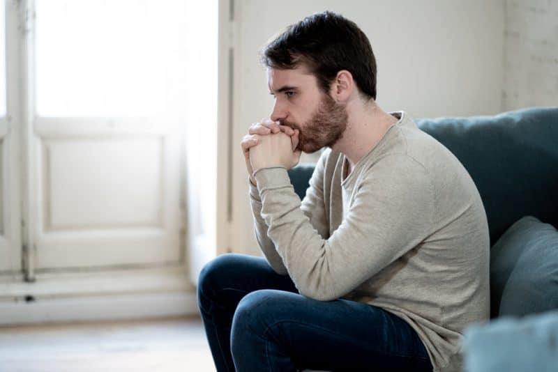 Olycklig deprimerad kaukasisk man som sitter och ligger i vardagsrum