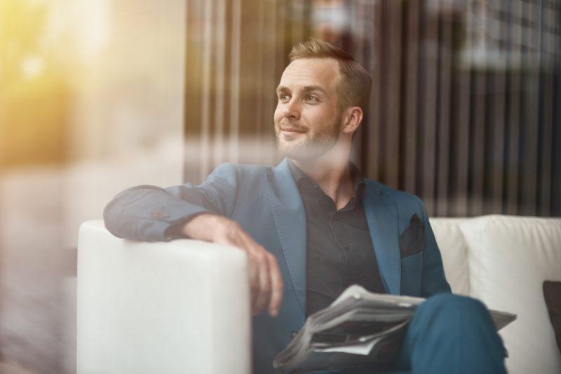 Positiv självpåstående affärsman som rymmer en tidning
