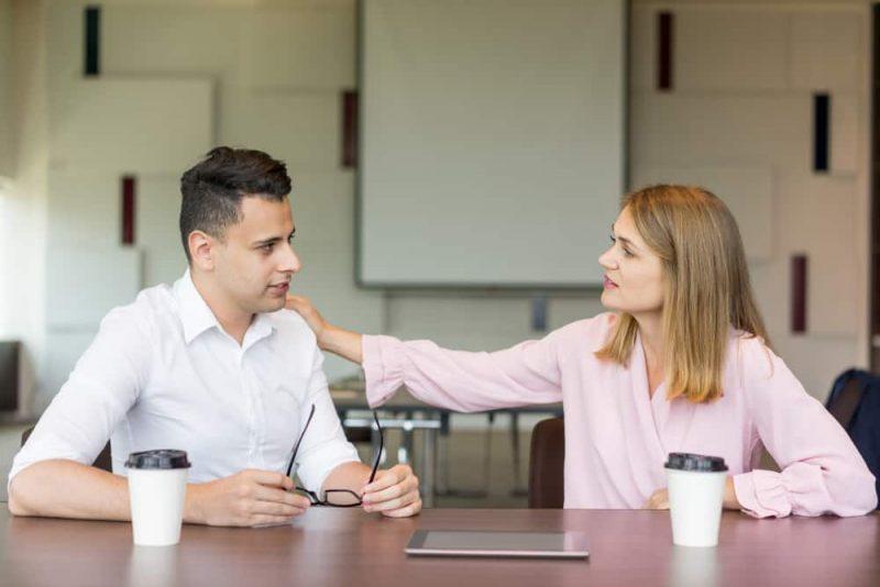 Säker affärskvinna som knackar på den manliga kollegan på axeln vid kaffepausen
