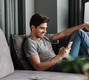 le ung skäggig man som bär casual kläder som sitter på en soffa i vardagsrummet och smsar