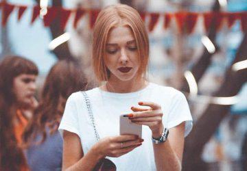 kvinna som står utanför skickar meddelande på telefon