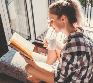 Ungt nätt kvinnasammanträde på det öppna fönstret som dricker kaffe och läser en bok tycker om vilar