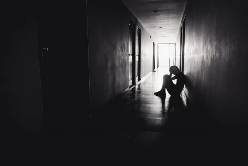Sorgligt deprimerat mansammanträdehuvud i händer på golvet