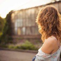 bakifrån av blond tjej som står utanför under dagtid