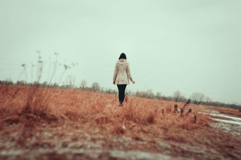 Ung flicka som går på gräsfält