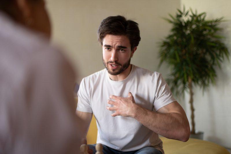 Ung skäggig man som pekar på bröstet och delar känslor
