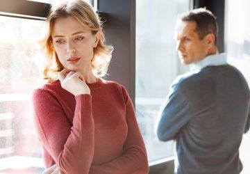 Ledsen olycklig gladlös kvinna som står nära sin pojkvän och håller hakan medan hon känner sig deprimerad