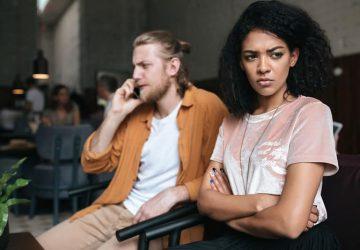 kvinna sitter upprörd på soffan medan man pratar i telefon
