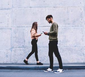 man och kvinna som går förbi varandra medan man håller telefoner