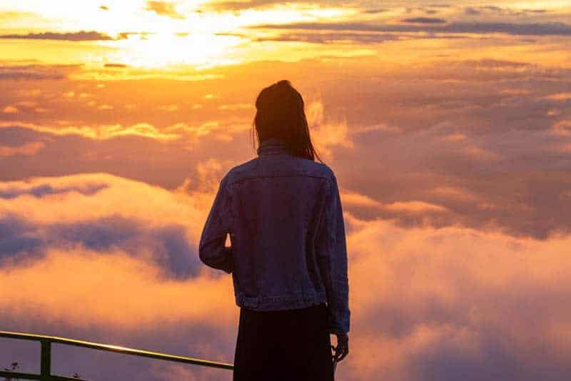 bakifrån av kvinna som står på toppen av kullen