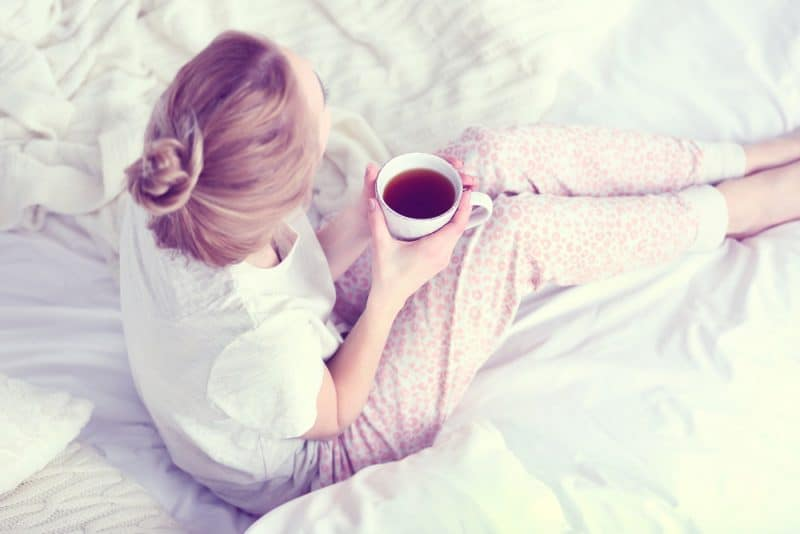 blond kvinna som sitter och dricker te