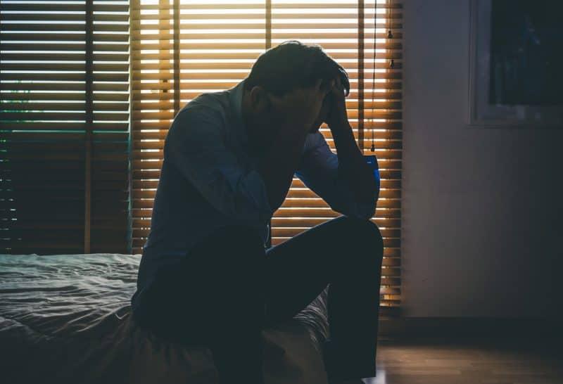 deprimerad man sitter huvudet i händerna på sängen i det mörka sovrummet