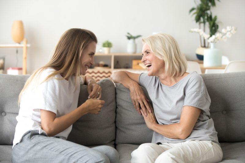 gammal mamma och ung vuxen kvinna som talar skrattar tillsammans
