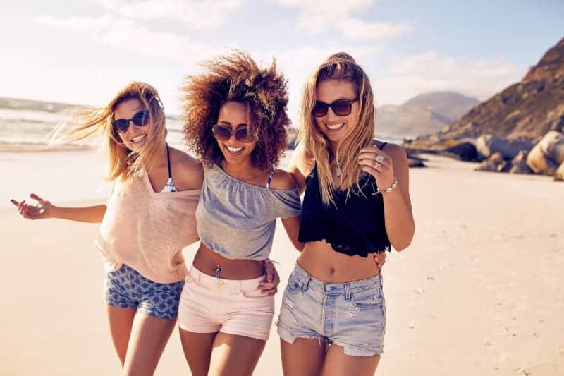 grupp vänner gå på sandstrand