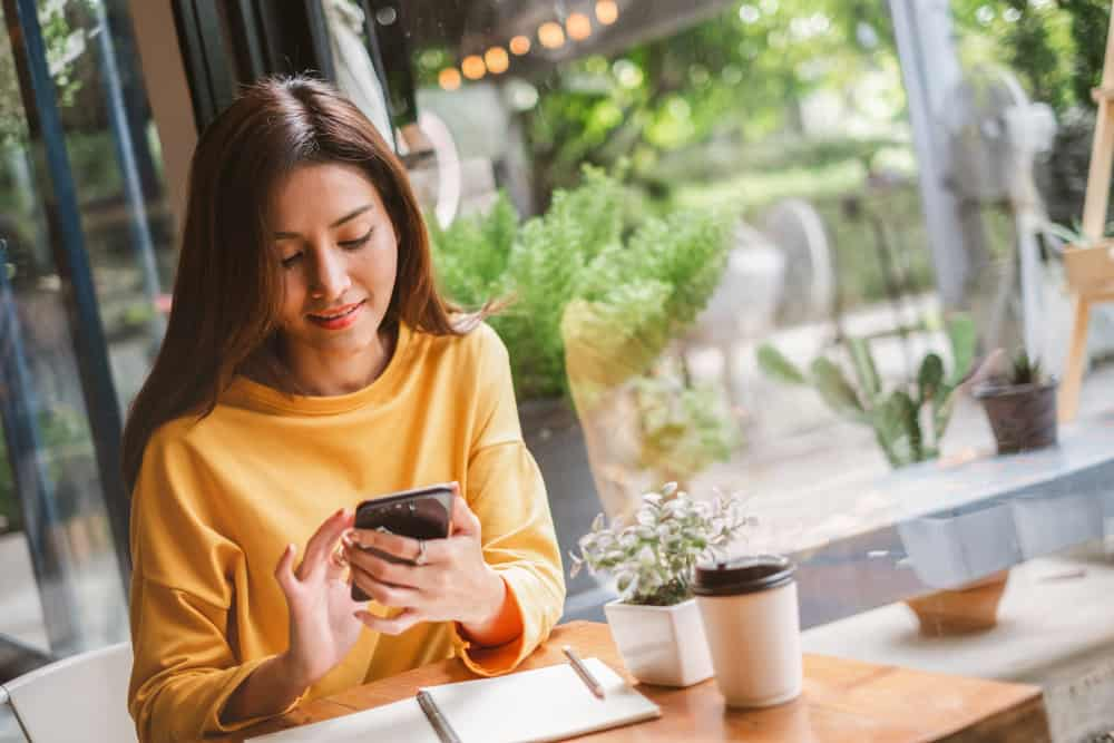 kvinna i gul skjorta som använder sin telefon i baren