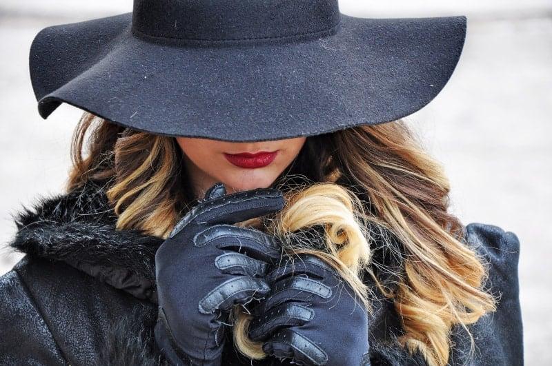 kvinna i svart kappa och svart hatt