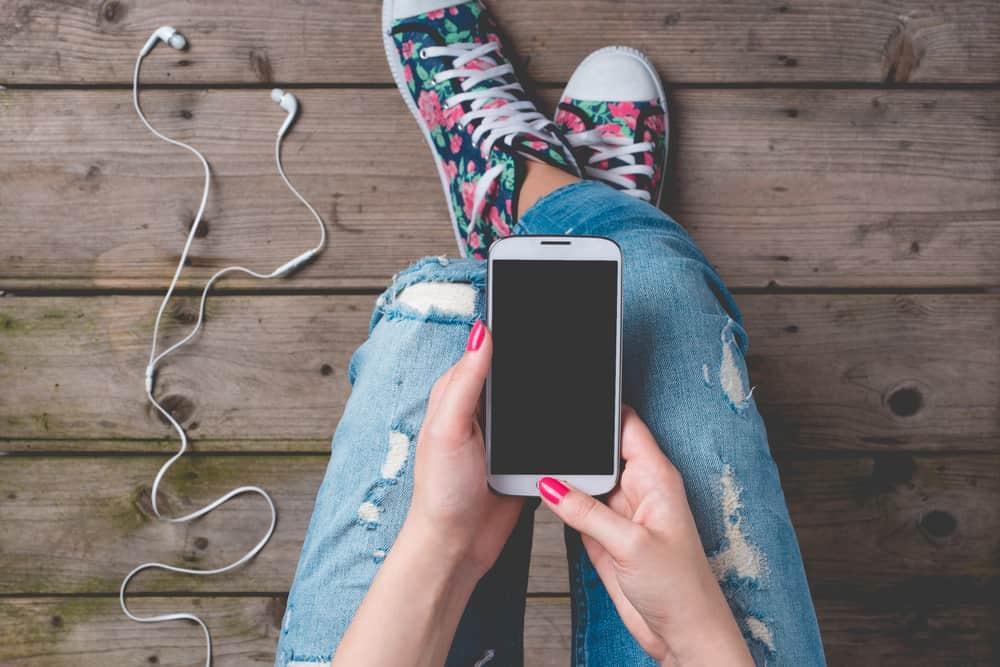 kvinna med färgglada skor som använder telefonen