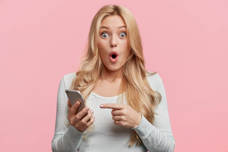 kvinna med telefon med rosa bakgrund
