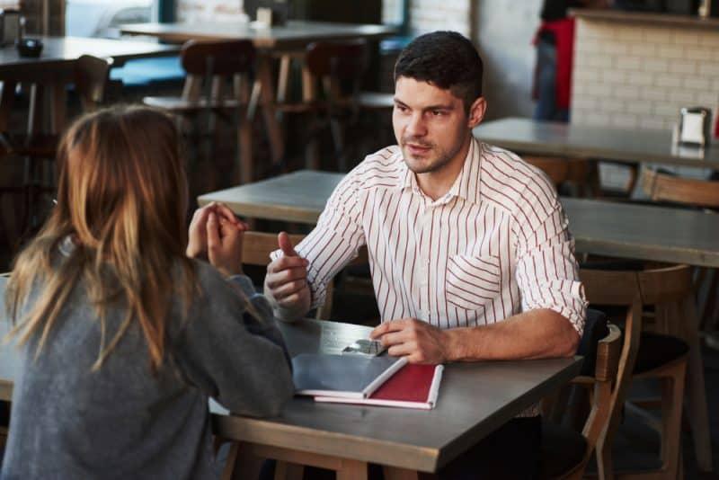 kvinna och man sitter vid bordet och pratar