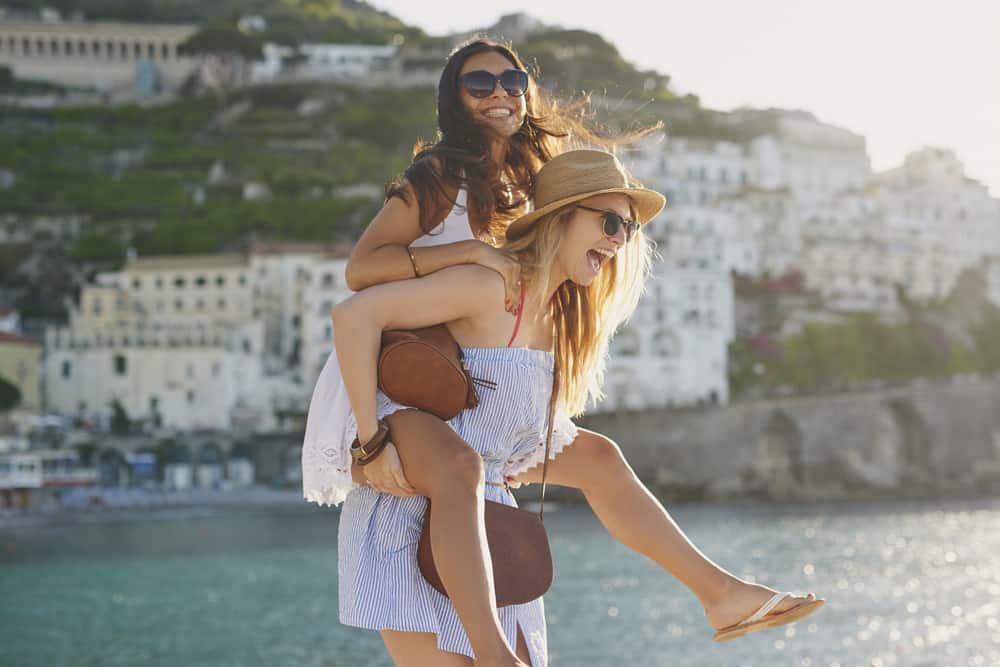 kvinna piggyback hennes vän nära vatten