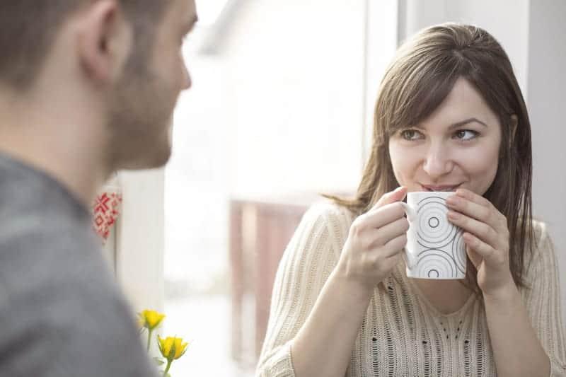 kvinna som flörtar med mannen medan hon dricker kaffe