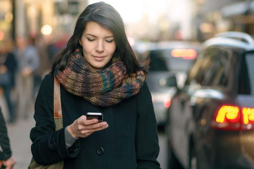 kvinna som går på gatan och använder sin telefon