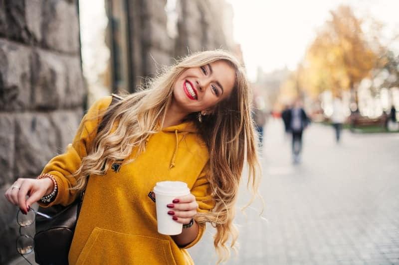 kvinna som håller kaffe på gatan