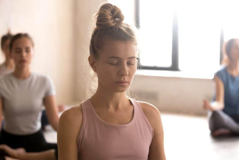 kvinna som mediterar med slutna ögon