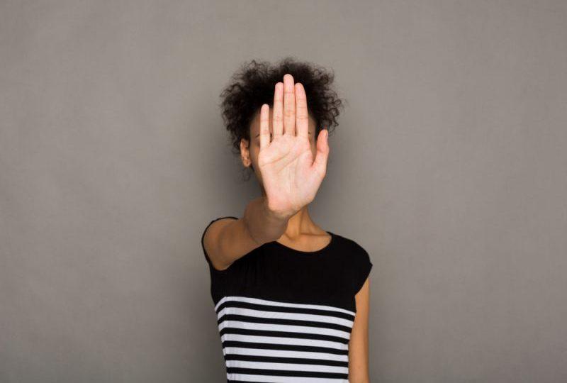 kvinna som täcker ansiktet med handflatan och säger nej