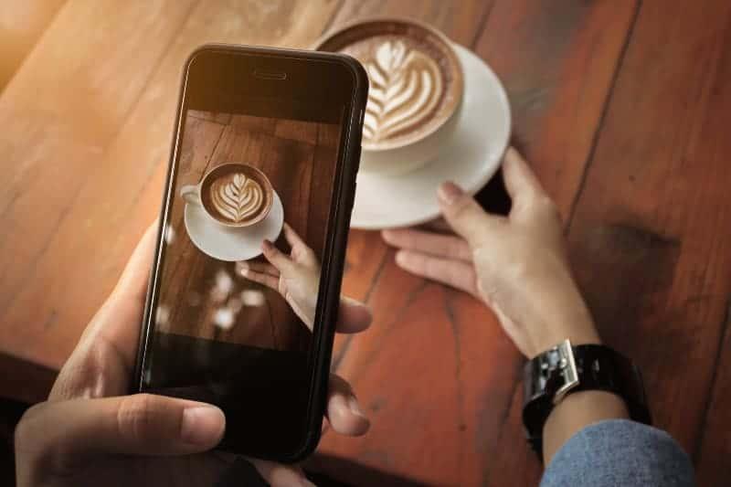 kvinna som tar foto av kopp kaffe