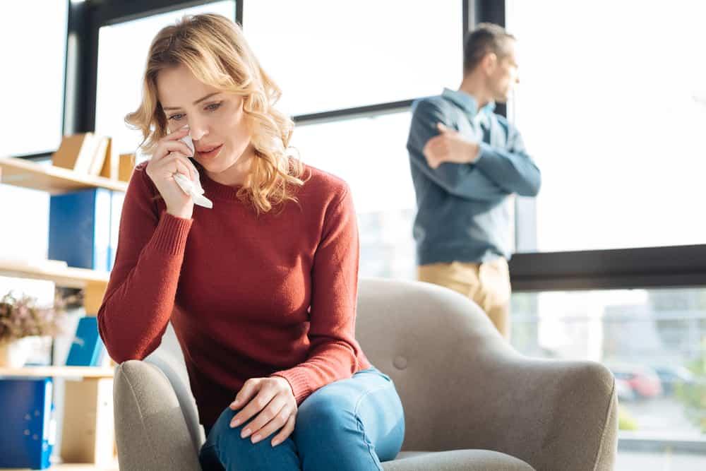 kvinnan gråter på soffan medan mannen ser genom fönstret