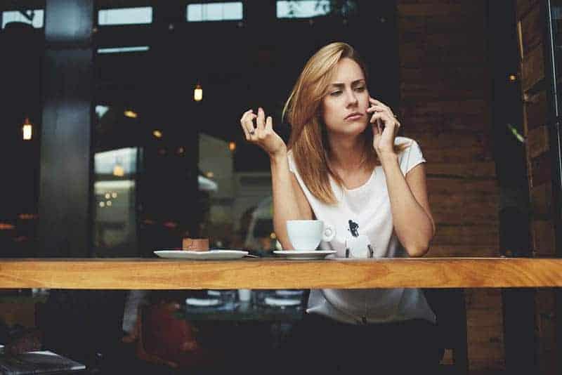 kvinnan ser omtänksam ut medan hon pratar i telefon på caféet