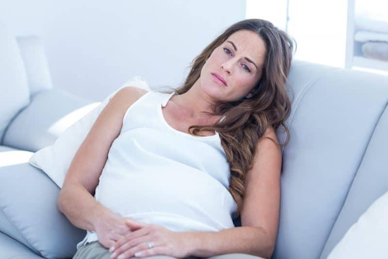 ledsen gravid kvinna som lutar sig på soffan hemma